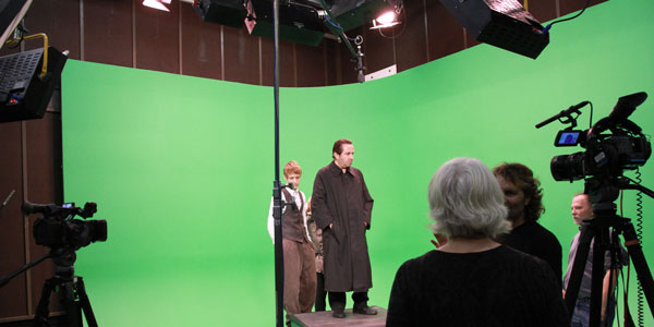 Actors and cameras next to green screen background